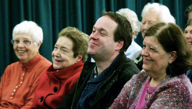 photo of church members, sitting in rows, smiling while listening to a speaker