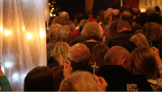 photo of people holding pipe cleaner crosses during church service