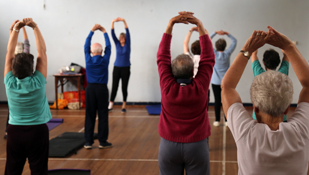 photo of people stretching their arms during friday fitness class