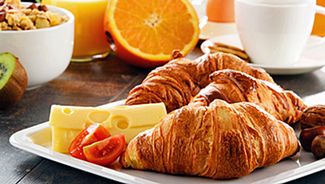 breakfast picture of croissant, cheese, fruit, muesli, juice and coffee