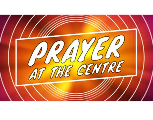 Prayer at the Centre logo - white text with concentric circles on red//orange/yellow background