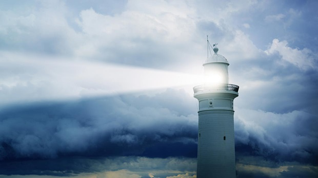 lighthouse shining through the clouds
