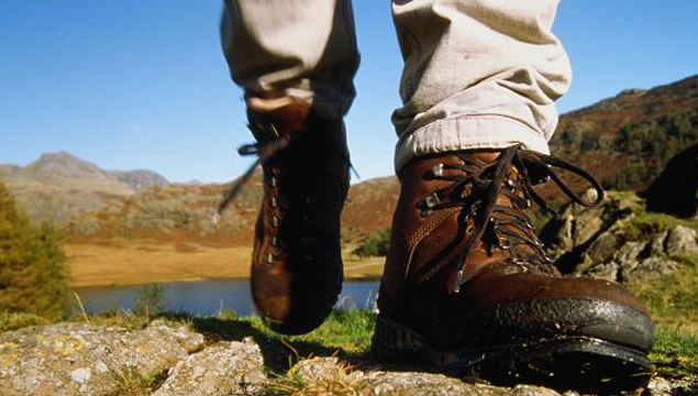 photo of feet in walking boots strolling through the countryside